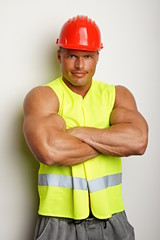 Muscular worker at protective helmet and work vest