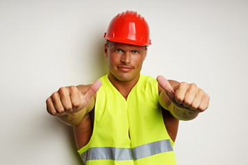 Muscular worker at protective helmet shows with fingers on you