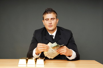 Young man in suit with gold bricks counts money
