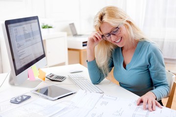 Blonde architect watching blueprint at the office