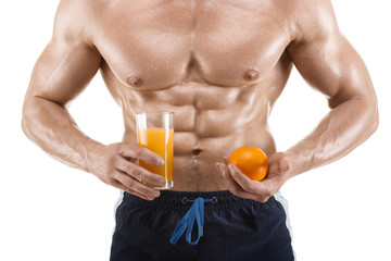 Muscular healthy man holding a glass with juice and orange