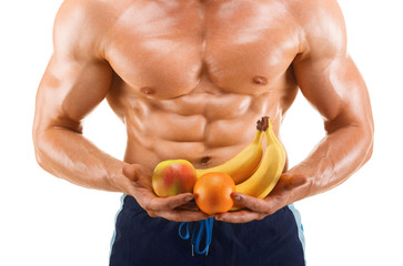 Muscular healthy man holding a fresh fruits, shaped abdominal