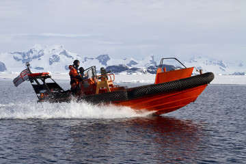 orange boat sailing at high speed in Antarctic waters against mo