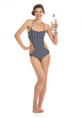Full length portrait of woman in swimsuit with bottle of water
