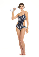 Happy woman in swimsuit with bottle of water