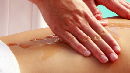 Beauty therapist massaging honey into womans back