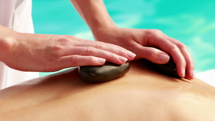Beauty therapist rubbing womans back with hot stones