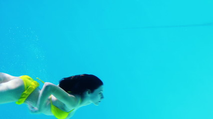 Brunette in yellow bikini swimming underwater