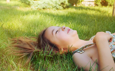 happy smiling little girl lying on the grass in sunny summer day