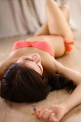 Beautiful woman in a swimsuit is lying on the floor