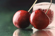 sweet delicious ripe cherries on green table with water drops ma
