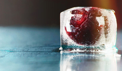 frozen delicious red cherry in ice on navy blue background