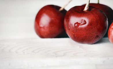 ripe delicious cherries on white wooden table with water drops m
