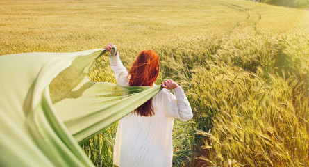 fashion red hair woman standing back hands up with green fabric