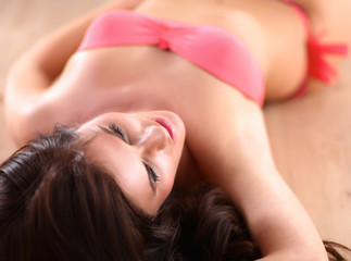 Beautiful smiling woman in a pink swimsuit is lying on the floor