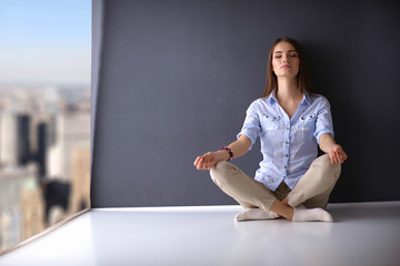 Young woman sitting on the floor near wall ,doing yoga