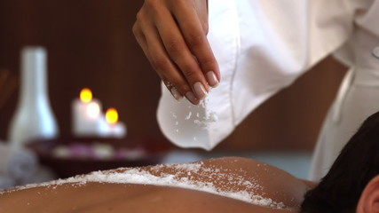 Beauty therapist pouring salt scrub on back