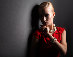 Young woman on red dress, isolated black background