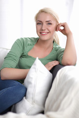 Beautiful smile young woman with white pillow sitting on the
