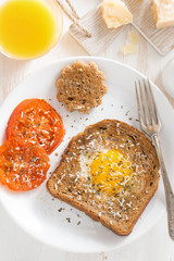 fried egg in a toast and grilled tomatoes, top view