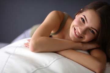 Closeup of a smiling young woman lying on couch