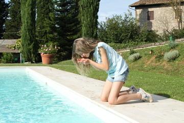 Bambina raccoglie acqua della piscina dal bordo