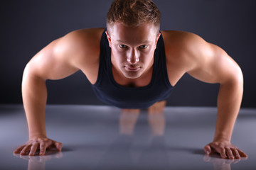 Muscular young man doing press-ups