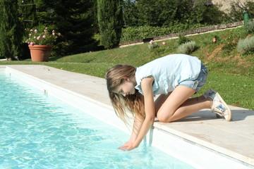 Bambina gioca con le mani dell'acqua dal bordo della piscina