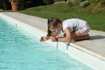 Bimba gioca con l'acqua della piscina