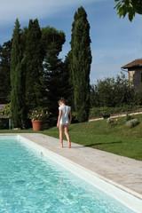 Bambina cammina sul bordo di una piscina