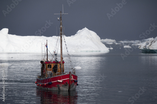 Red fishing boat around icebergs at Disko Bay, Ilulissat