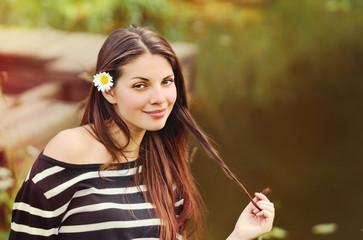 cute beautiful woman with chamomile in long hair enjoying harmon