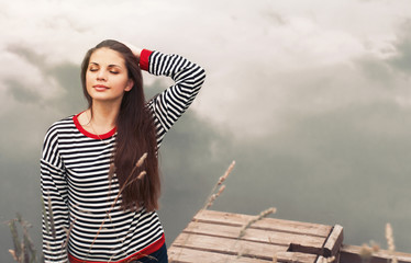 cute attractive young woman enjoying harmony of nature on pier n