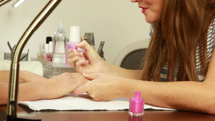 Nail technician applying nail varnish to customers nails
