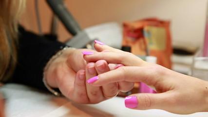 Nail technician painting top coat onto customers pink nails