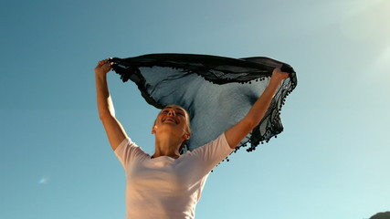 Happy woman holding black scarf above head on sunny day