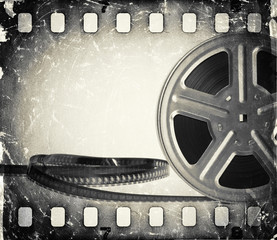 Grunge old motion picture film reel with film strip.