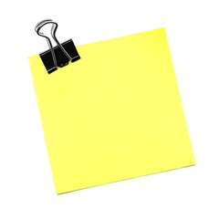Single yellow post it note with paper clip isolated on white