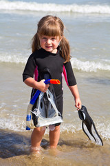happy girl on beach with colorful face masks and snorkels, sea i