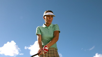 Lady golfer swinging her club