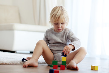 Toddler playing with wooden blocks