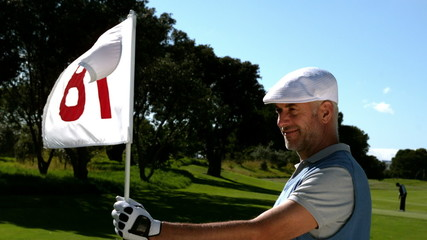 Smiling golfer holding eighteenth hole flag on golf course