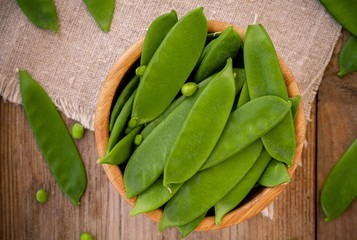 young green peas pods in a bowl on a wooden background
