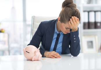 Frustrated business woman with piggy bank