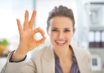 Closeup on happy business woman showing ok gesture