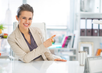Happy business woman in office pointing on copy space