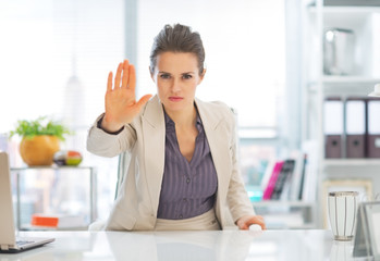 Business woman in office showing stop gesture