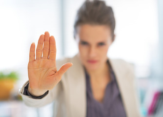 Closeup on business woman in office showing stop gesture