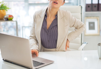 Closeup on business woman with back pain