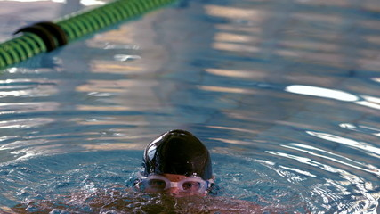 Fit muscular swimmer emerging from the pool